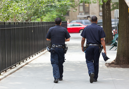 NEW YORK CITY , USA - JULY 07, 2015: Two police officers from the back in the center of Manhattan.. NYPD, established in 1845, is the largest municipal police force in the United States.