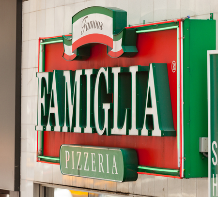 Foto per New York City, Usa - July 07, 2015: Lighted sign of famous pizzeria Famiglia in Manhattan, typical italian restaurant in NYC. - Immagine Royalty Free