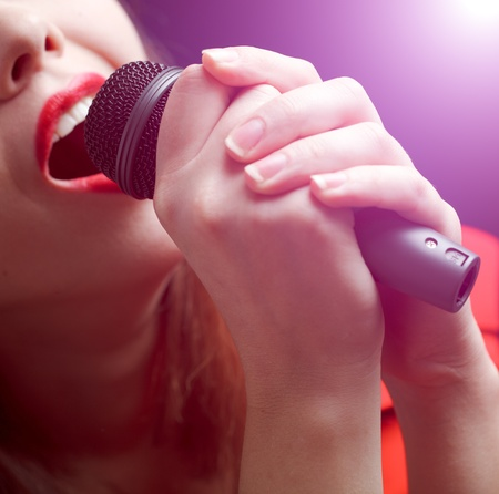 Woman sing over color background. Focused on microphone