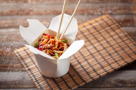 Photo pour Noodles with pork and vegetables in take-out box on wooden table - image libre de droit