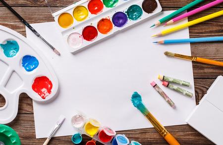 Photo pour Paper, watercolors, paint brush and some art stuff on wooden   table. Top view. - image libre de droit