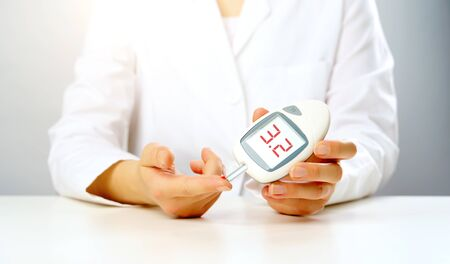 Photo pour Photo of doctors hand with a glucometer with inscription three in studio on gray background - image libre de droit