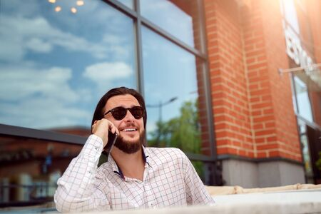 Photo for Photo of young man talking on phone sitting in street cafe in city on summer afternoon - Royalty Free Image