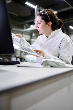 Photo pour Serious woman lab technician sitting at table with computer and carbon mesh - image libre de droit