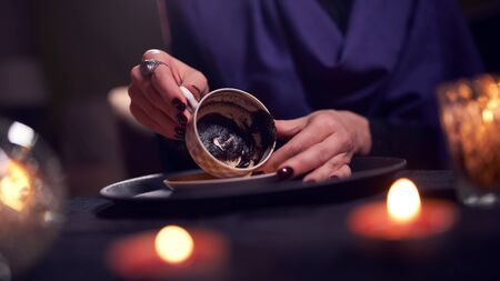Photo pour Female fortune teller divines on coffee grounds at table with ball of predictions - image libre de droit