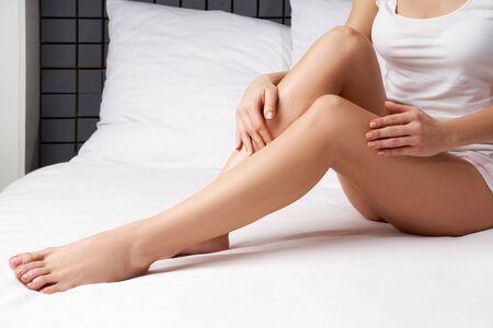 Photo pour Legs and arms of unrecognisable woman sitting on bed - image libre de droit