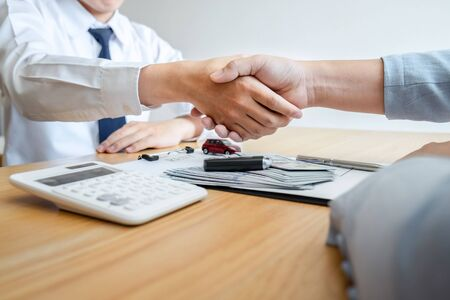 Photo pour Car rental and Insurance concept, Young salesman shaking hands with customer after sign agreement contract with approved good deal for rent or purchase. - image libre de droit