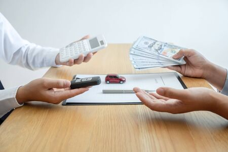 Photo pour Car rental and Insurance concept, Young salesman receiving money and giving car's key to customer after sign agreement contract with approved good deal for rent or purchase. - image libre de droit