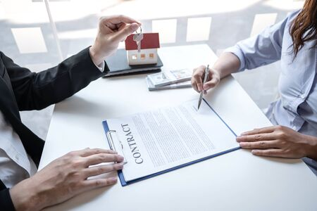 Photo pour Real estate agent are presenting home loan and sending keys to customer after signing contract to buy house with approved property application form, Insurance Home concept. - image libre de droit