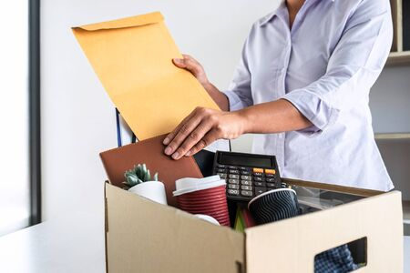 Photo for Images of stress of woman employee has a brown cardboard box and intend sending resignation letter to boss employer consider in order to contract for quit or layoff of job leaving from work. - Royalty Free Image