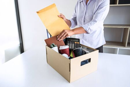 Photo pour Images of stress of woman employee has a brown cardboard box and intend sending resignation letter to boss employer consider in order to contract for quit or layoff of job leaving from work. - image libre de droit