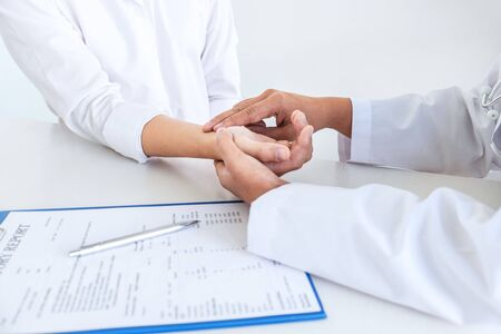 Photo pour Doctor checking measuring pressure on patient's hand pulse by hands, Medical and healthcare concept. - image libre de droit
