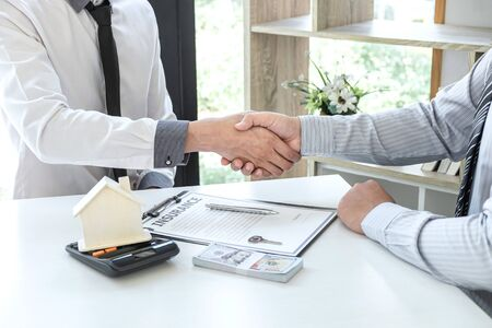 Photo pour Real estate agent are shaking hands after good deal and giving house, keys to customer after signing contract to buy house with approved property application form. - image libre de droit