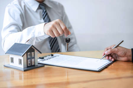 Photo pour Home Insurance and Real estate investment concept, Sale agent giving house key to new client after signing agreement contract with approved property application form. - image libre de droit
