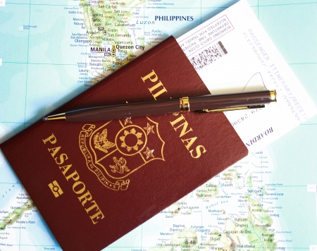 Philippines passport with pen and boarding pass over map background