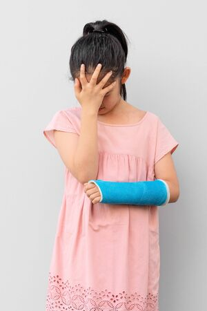 Photo pour Asian Child with Broken Arm in Cast with Hurting and Sad Face Expression - image libre de droit