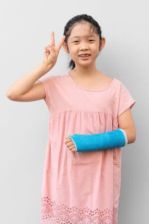Photo pour Asian Child with Broken Arm in Cast with Smiling Face Expression - image libre de droit
