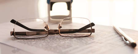 Photo for Stamping contract, spectacles glasses, pen and stamp on contract on white glossy table. banner - Royalty Free Image