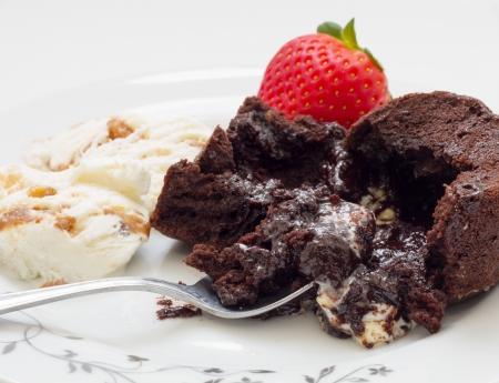 Chocolate cake volcano with creamy ice cream and strawberries.