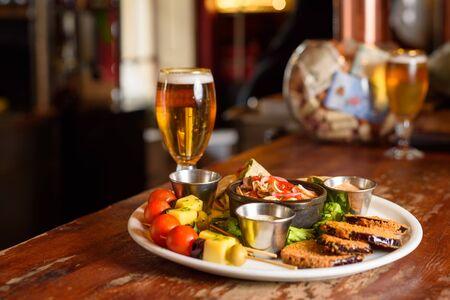 Photo pour a Chilean meat platter with a cold beer - image libre de droit