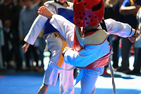 Kids fighting on stage during Taekwondo tournament