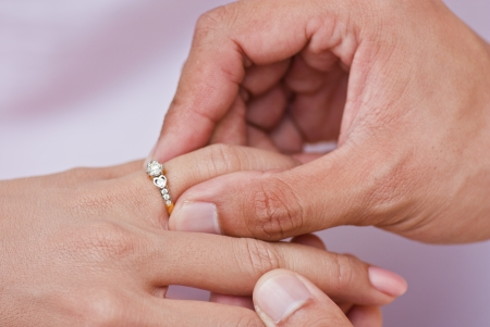 Photo for Male hand wear diamond ring in to female finger - Royalty Free Image