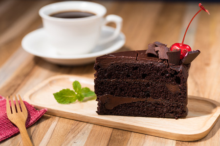 Photo pour chocolate cake on wooden table with a coffee cup - image libre de droit
