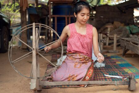 Photo pour Young Asian woman spinning cotton thread by hand - image libre de droit