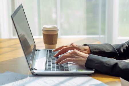 Foto de Close up of a businesswoman hands typing in a laptop in the office with cup of coffee, business concept - Imagen libre de derechos
