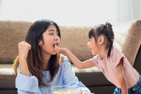 Photo pour Happy Asian child enjoy eating popcorn with her older sister, love and happiness family concept - image libre de droit