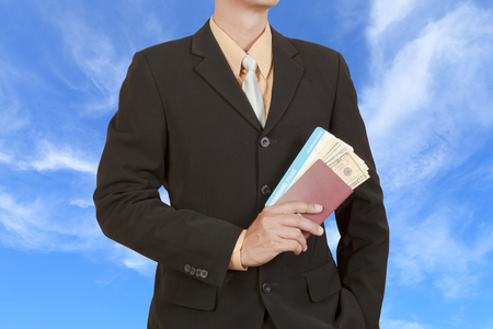 Businessman hold passport, boarding pass and dollar on blue sky background