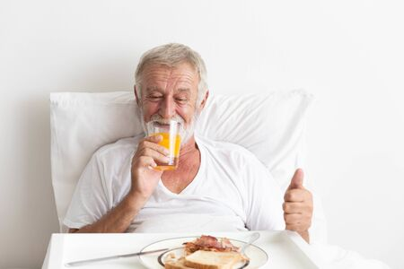 Photo for Senior retirement male happy having breakfast with orange juice and water on bed - Royalty Free Image