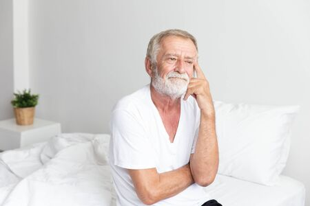 Photo pour Portrait of a senior retirement man sitting and thinking alone on bed in his home - image libre de droit
