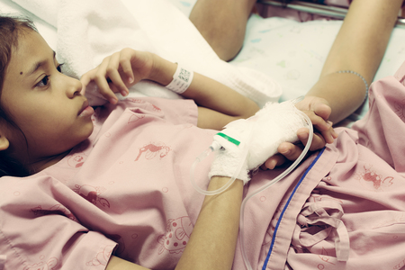 Photo pour Young daughter sick in hospital and her hand is holding by her mother with care - image libre de droit