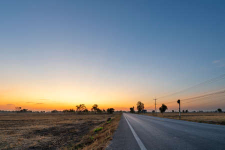Photo for Golden beautiful Sunrise clear with dry grass fields and long asphalt road & electric pole in the countryside at morning on quiet day - Royalty Free Image