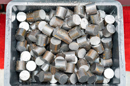 Photo for Top view many round shaft steel piece after cutting by automatic continuous and high speed band saw or circular saw machine in box - Royalty Free Image