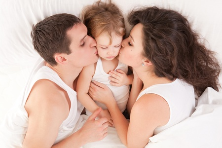Happy family, mother, father and daughter on the white bed