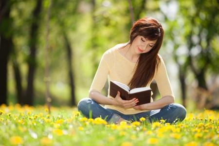 Photo pour Young woman reading a book in the park with flowers - image libre de droit