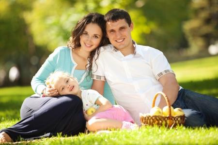 Foto de Happy family having a picnic in the green garden - Imagen libre de derechos