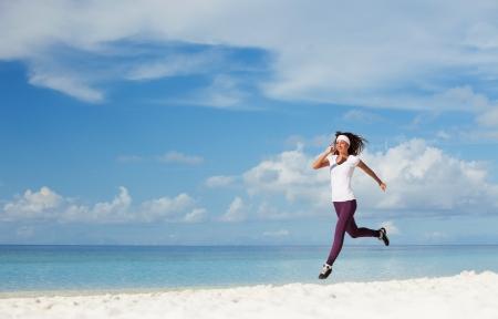 Foto de Young woman running on the beach - Imagen libre de derechos
