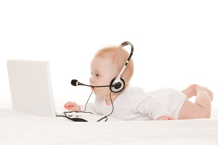 Photo for Cute baby-operator with laptop on the white bed - Royalty Free Image