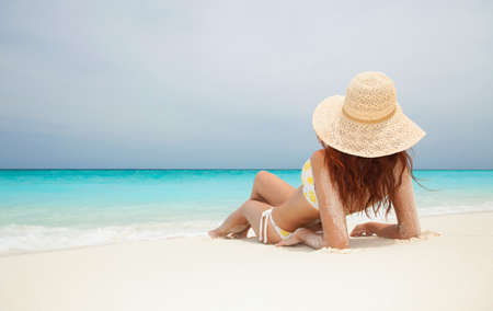 Photo pour Young fashion woman im straw hat relax on the beach. Happy lifestyle. White sand, blue sky and crystal sea of tropical beach. Vacation at Paradise. Ocean beach relax, travel to islands - image libre de droit
