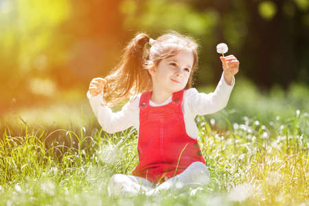 Photo pour Cute little girl play in the park with flowers. Beauty nature scene with colorful background at summer or spring season. Family outdoor lifestyle. Happy girl relax on green grass - image libre de droit