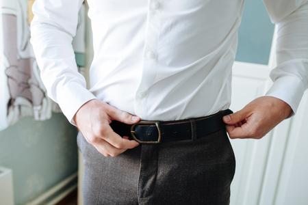 Foto de The man in brown trousers and a white shirt fastened a black leather trouser belt. Men's formal outfit. Fashion - Imagen libre de derechos
