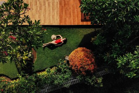 Photo pour Beautiful slim woman in red bikini and straw hat lies on green grass in garden near swimming pool, sunbathing, enjoys. . view from above. - image libre de droit