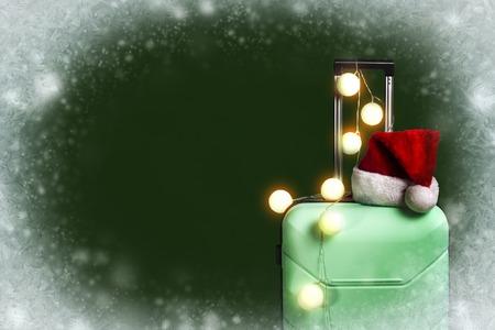 Foto de Plastic suitcase, Santa hat and garland on a dark green background with snow. - Imagen libre de derechos