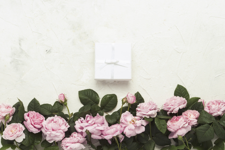 Photo for Pink roses, White gift box on a light stone background. flat lay, top view. - Royalty Free Image