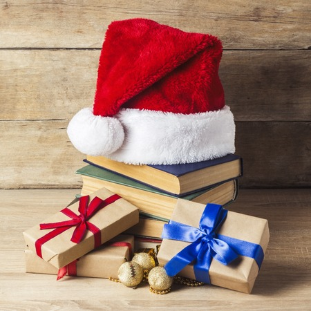 Photo for A stack of books, Santa Claus's cap, gift boxes with red and blue ribbons on a wooden background. Concept of New Year and Merry Christmas - Royalty Free Image