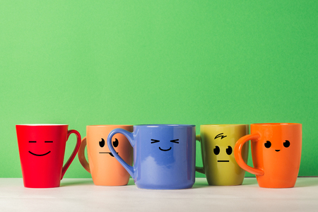 Foto de A lot of multicolored cups with funny faces on a green background. The concept of a friendly company, a big family, meeting friends for a cup of tea or coffee, father's day, office, boss day - Imagen libre de derechos