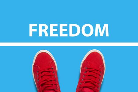 Photo for Female legs in red sneakers standing in front of the white line with the text Freedom behind the line. Concept of limiting freedom and action. Flat lay, top view. - Royalty Free Image